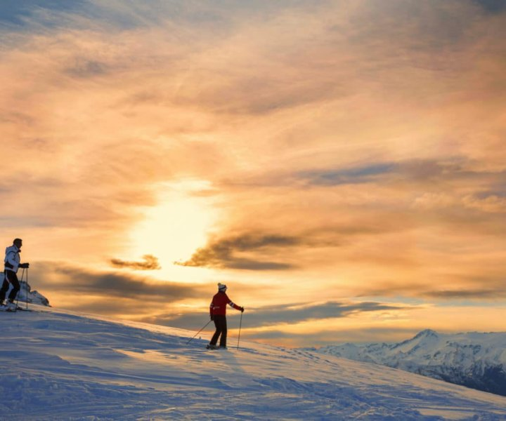 Snow skiers couple, off piste skiing. Mature women and men enjoying a beautiful winter mountains  sunset landscape. The  orange sky in the background.
